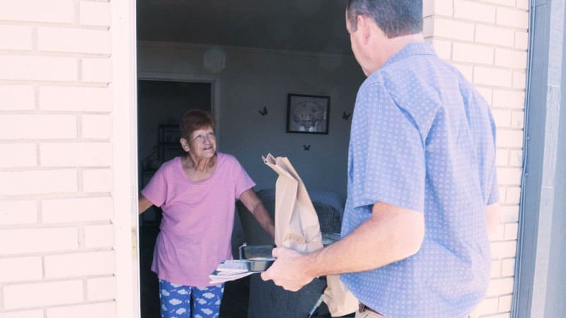 lady receiving food from volunteer